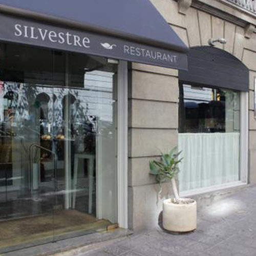 Entrance restaurant Silvestre Barcelona with the logo of the blue Dolphin Store at the door