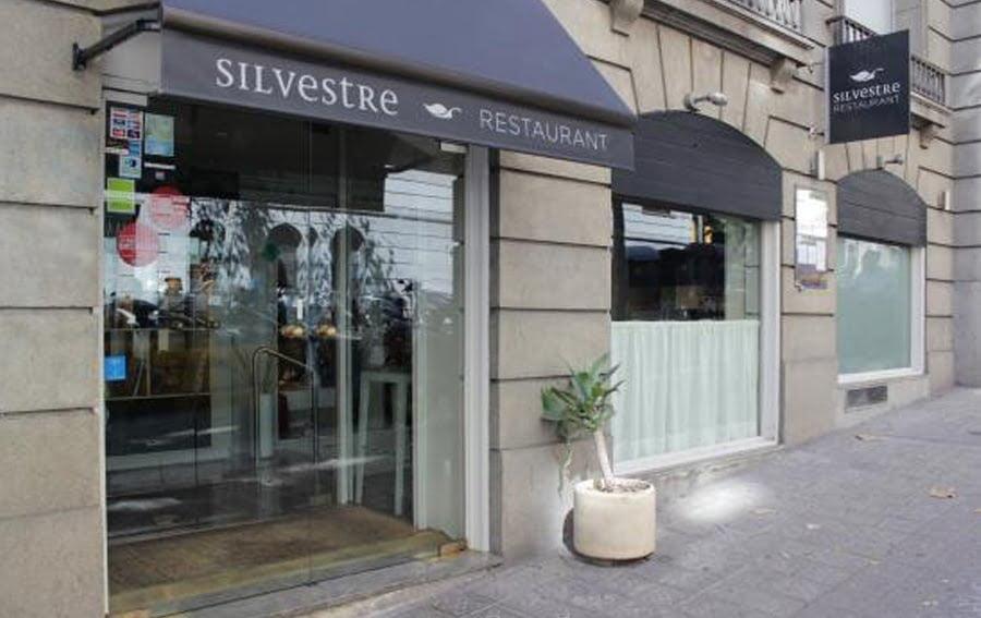 Entrada del restaurant Silvestre de Barcelona amb el logo de The Blue Dolphin Store a la porta