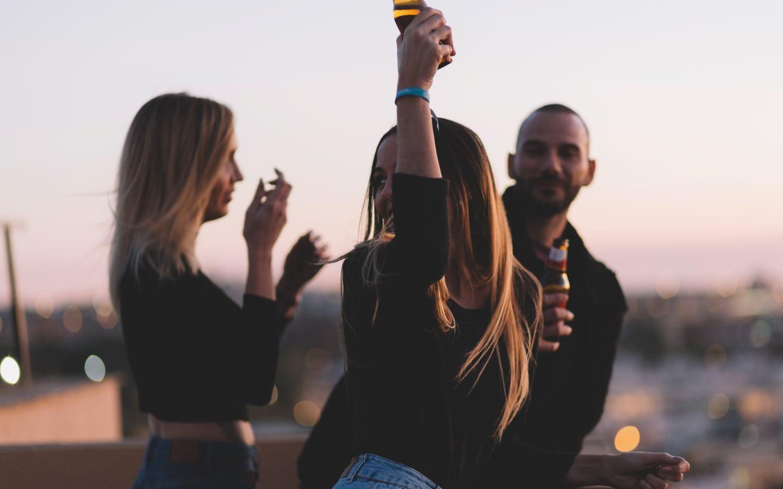 The Blue Dolphin Store imagen lifestyle de tres personas en una fiesta, en medio una chica con una botella de cerveza sin alcohol en a mano